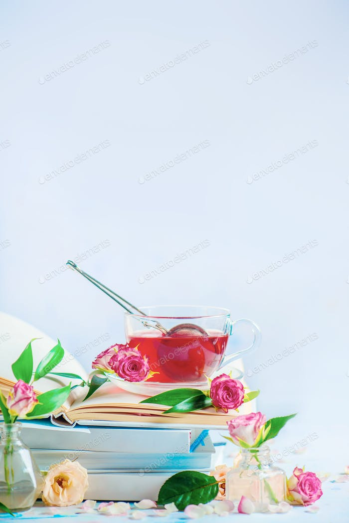 Leisure and reading concept on a white background with copy space. Stack of white books with a cup