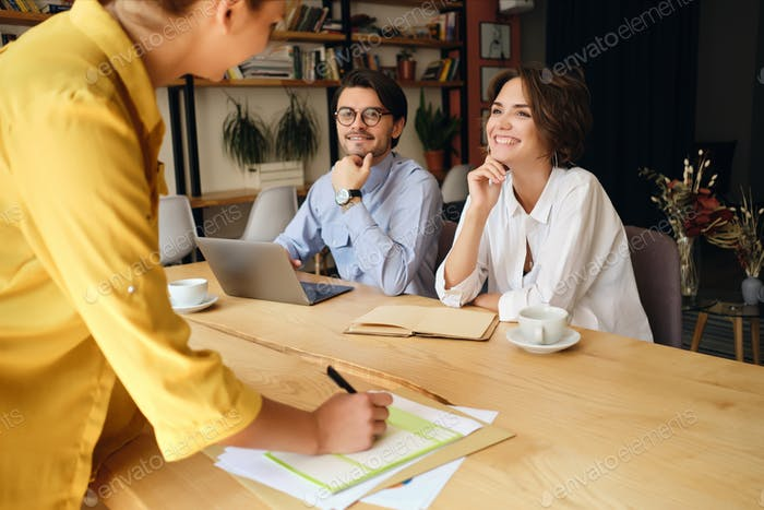 Smiling business colleagues sitting at the desk with papers joyfully talking at work in office