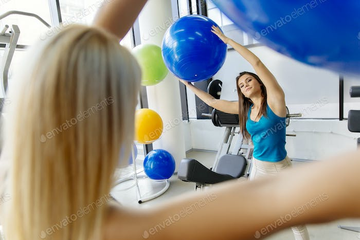 Women, friends training in gym and stretching