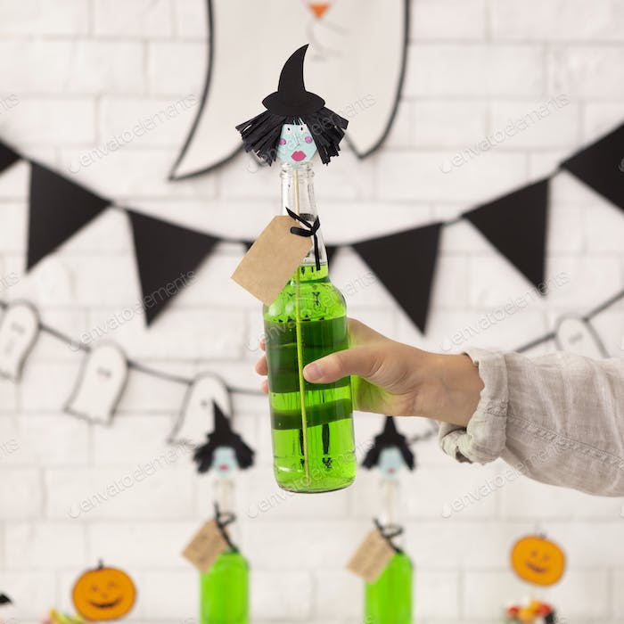 Green cocktail with cute witches head in woman hand