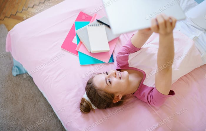 Young girl with tablet sitting on bed, relaxing during quarantine