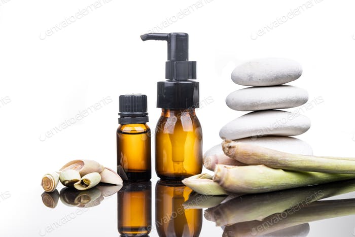 Lemongrass essential oil extract in bottle with fresh lemongrass plant and stacked rock as prop in