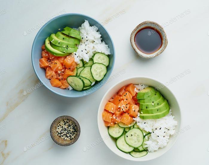 Lachs Poke Schüssel mit frischem Fisch, Reis, Gurke, Avocado