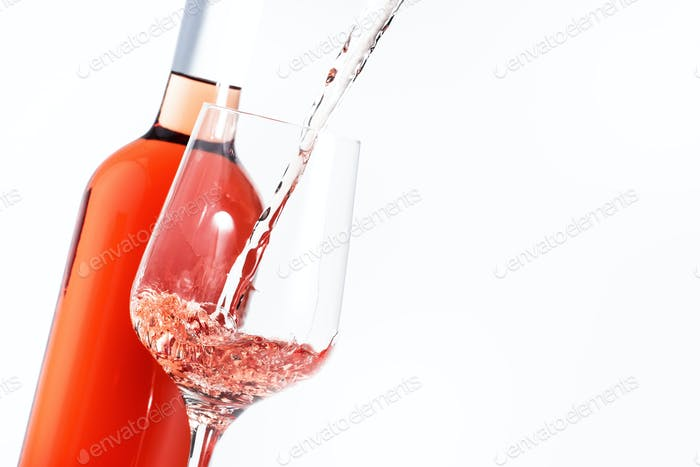 Rose wine pouring out of the bottle, white background