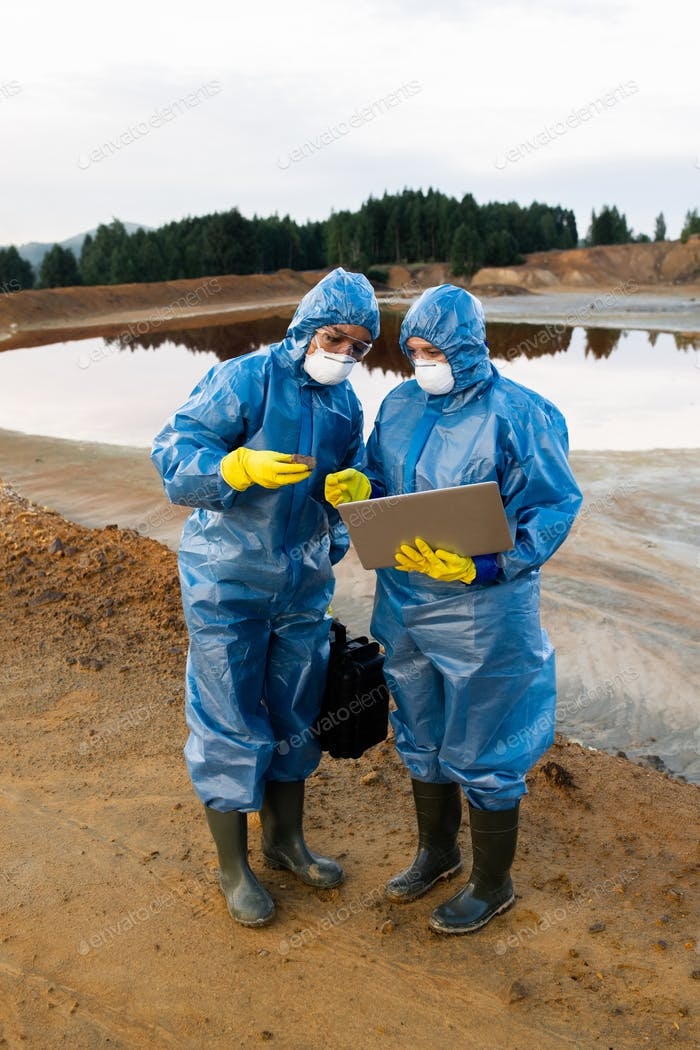 Young female ecologists in protective workwear standing on polluted soil or clay