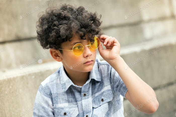 Young curly headed boy with trendy yellow shades