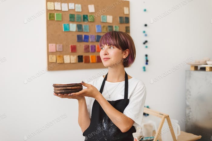 Pretty girl with colorful hair in black apron and white T-shirt holding handmade plates in hands