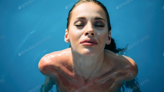 Exotic beautiful woman sunbathing and swimming