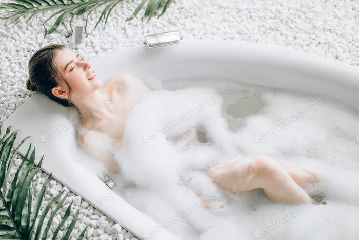 Thumbnail for Attractive lady lying in bath with foam, top view