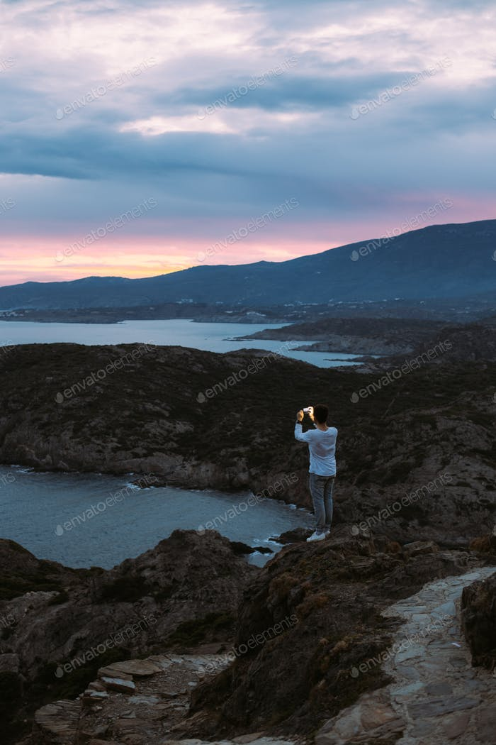 man makes photo of epic landscape sunset