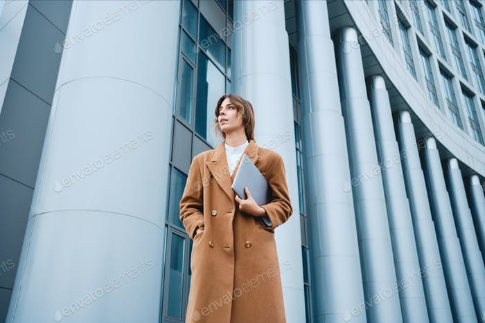 Young confident stylish businesswoman in coat with laptop intently looking away outdoor