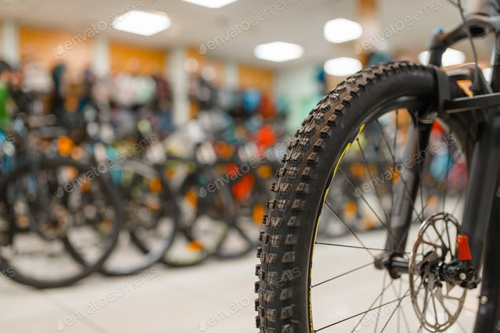 Bicycle in sports shop, focus on front wheel