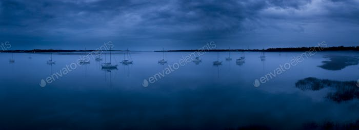 fog on glassy water with sailboats, panoramic shot.