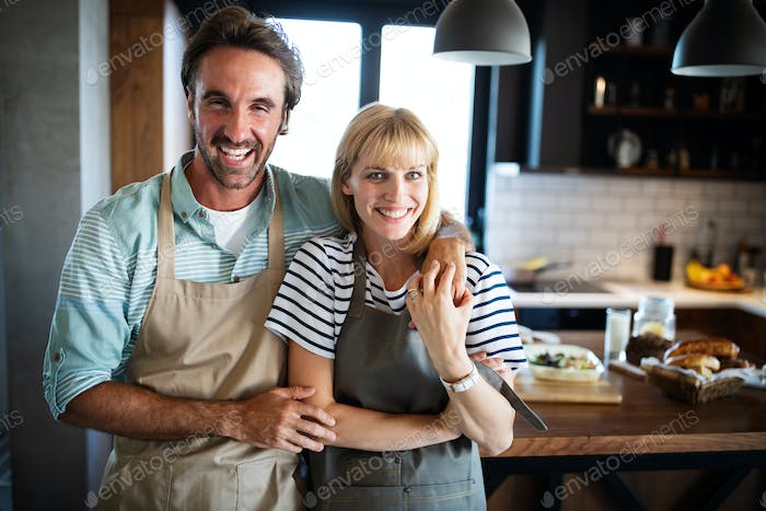 Happy couple cooking together. Husband and wife in their kitchen at home preparing healthy food