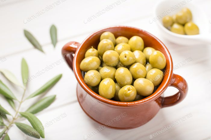Green olives on rustic bowl
