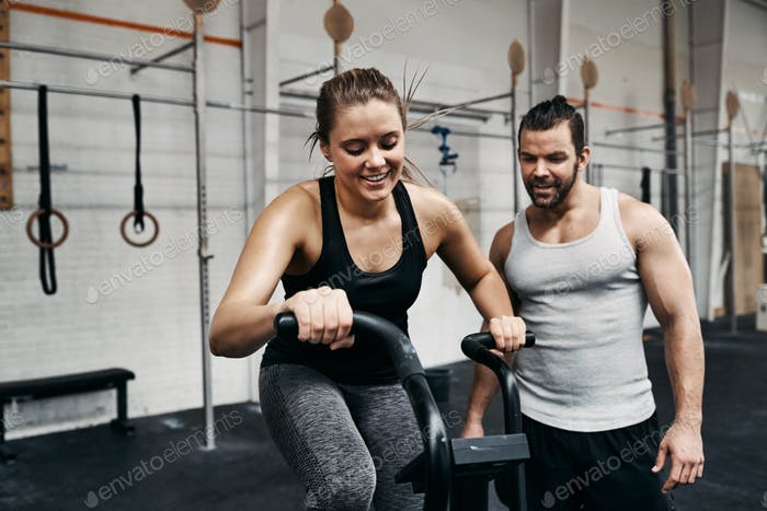 Smiling young woman riding a gym bike with her partner