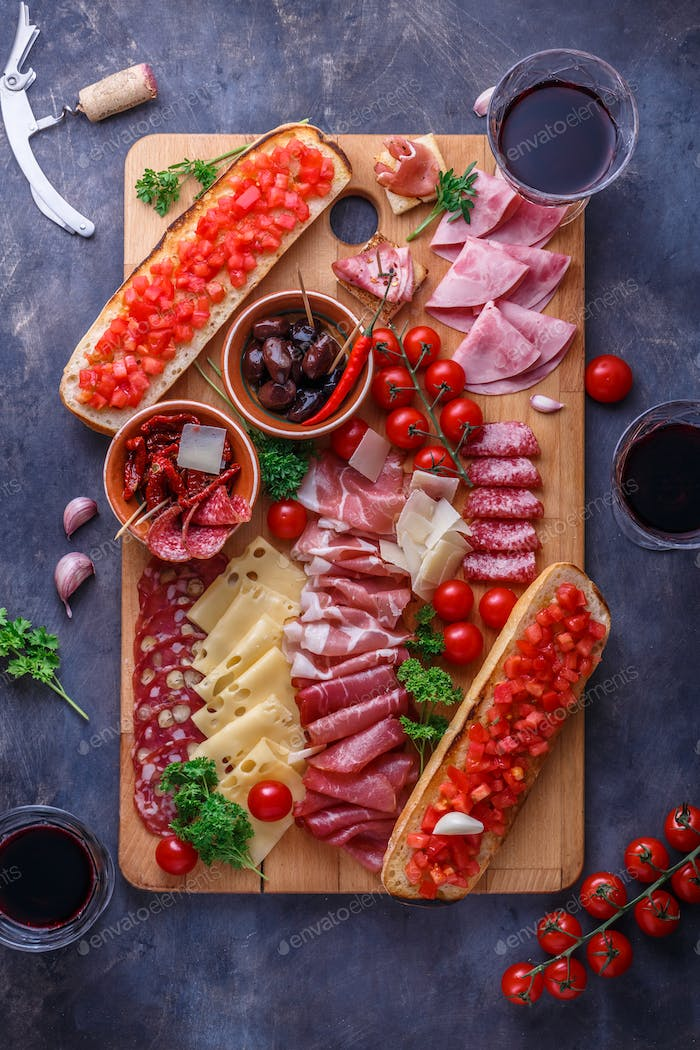 Board of cured meat, cheese and bread with wine