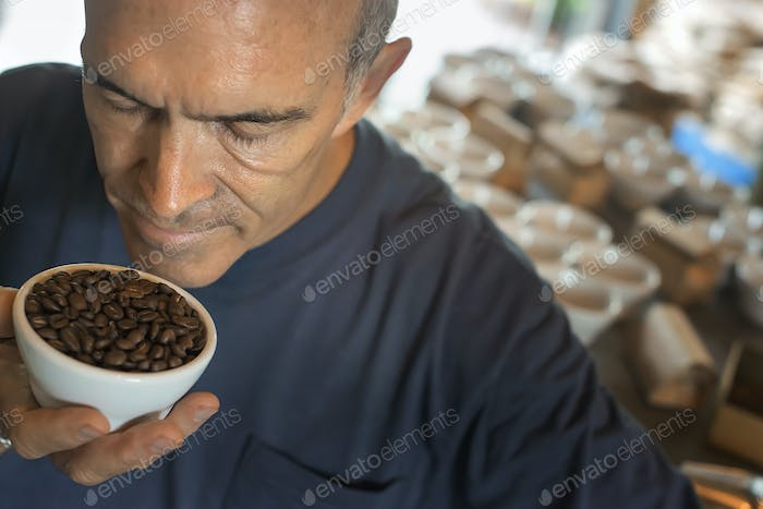 Man sampling coffee in a coffee processing shed.