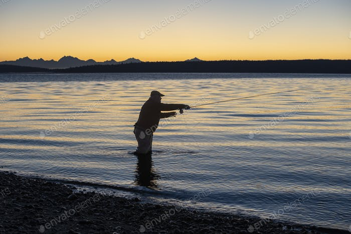 A silhouette of a fly fisherman casting at sunrise for searun coastal cutthroat trout on a beach on