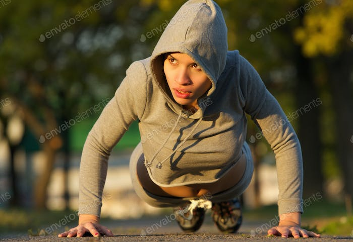 Attractive young woman doing push ups outdoors