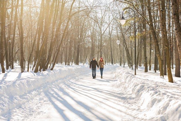 glückliches Paar zu Fuß durch einen verschneiten Wald im Winter