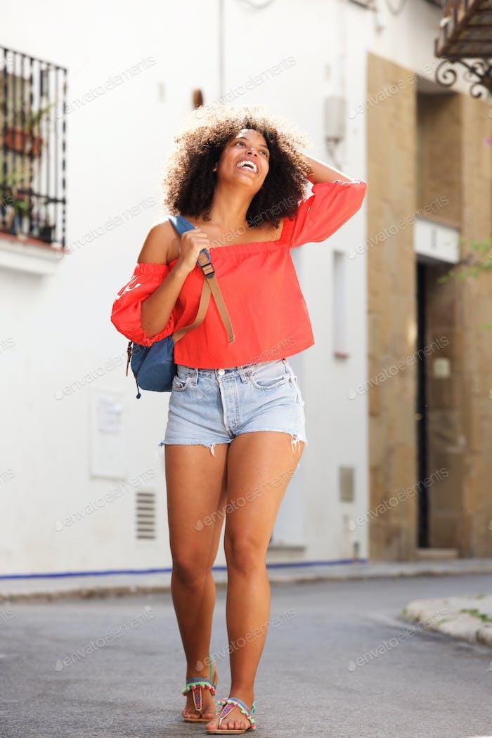 In voller Länge lachende Frau stehend auf der Straße mit Rucksack