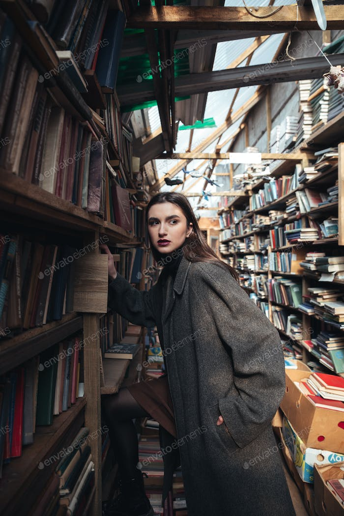 Fashionable woman climbing on a stairs in a book warehouse