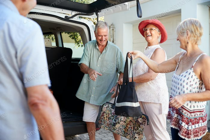 Group Of Senior Friends Loading Luggage Into Trunk Of Car About To Leave For Vacation