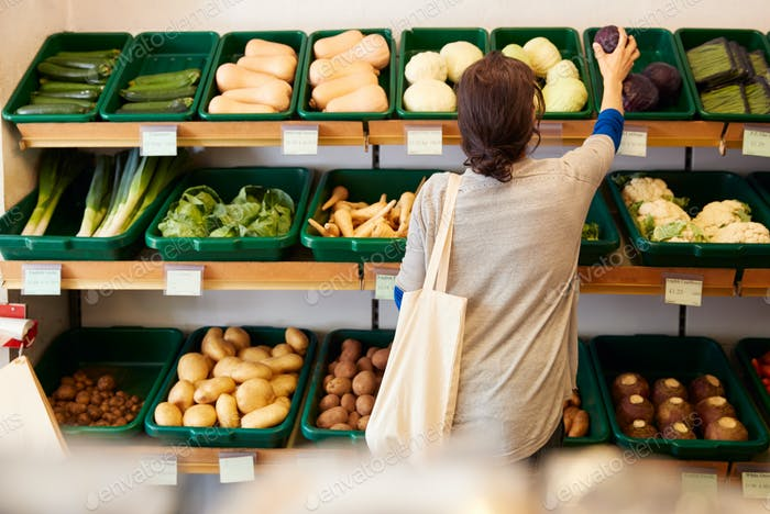Rear View Of Female Customer Choosing Fresh Produce In Organic Farm Shop