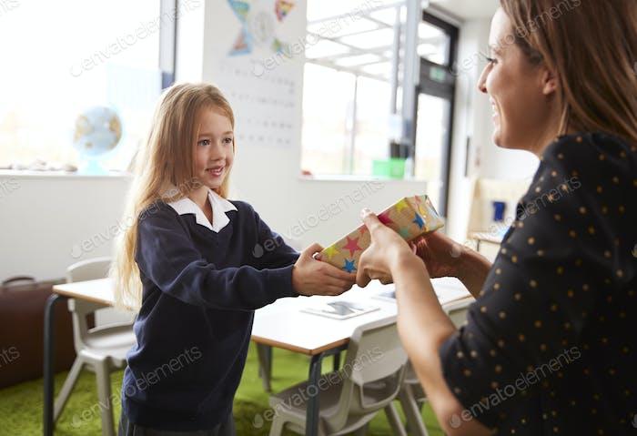 Schulmädchen in einer Grundschule präsentiert ein Geschenk an ihre weibliche Lehrerin in einem Klassenzimmer, Nahaufnahme
