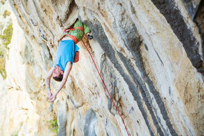 Young man resting while climbing challenging route