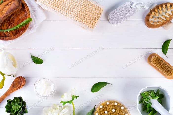 Spa treatment concept with green leaves, natural cosmetic products and massage brush on white wooden