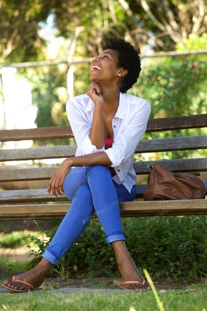 African woman laughing on a park bench