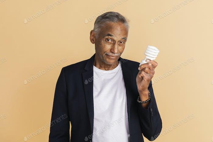 Mixed Indian senior man holding a light bulb