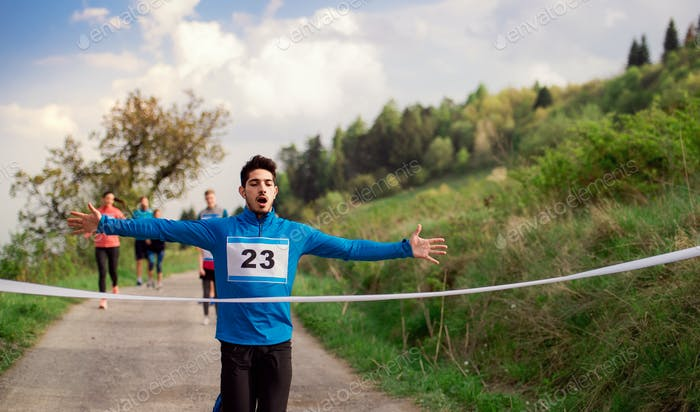 Man runner crossing finish line in a race competition in nature