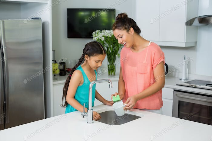 Mother assisting her daughter in cleaning vessel