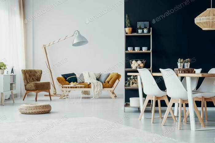 Chairs at dining table in white and black apartment interior wit
