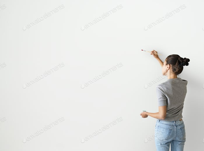 Artist woman painting the wall