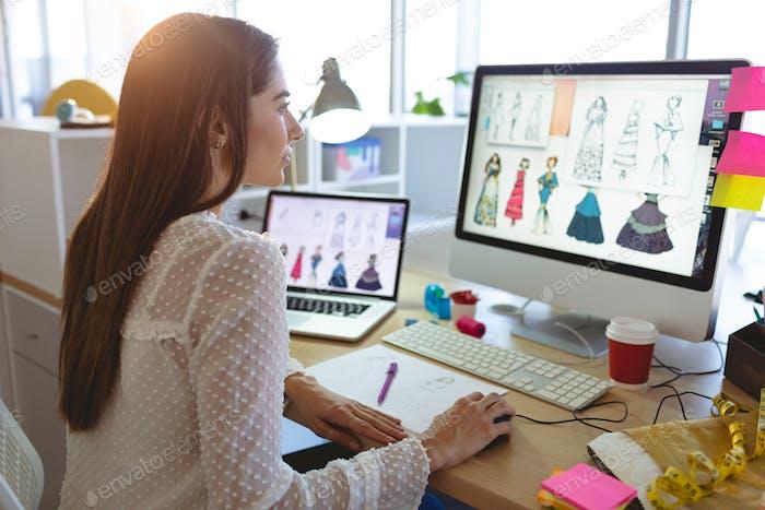 Seitenansicht der jungen kaukasischen weiblichen Modedesignerin arbeitet am Computer am Schreibtisch in einem modernen Büro