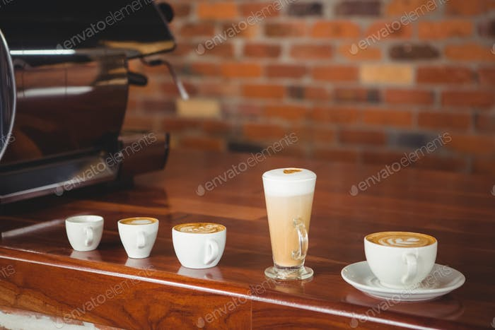 Several hot beverages in a row on the counter at coffee shop