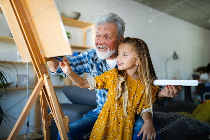 Happy smiling grandfather and grandchild painting together. Family, generation, happiness concept