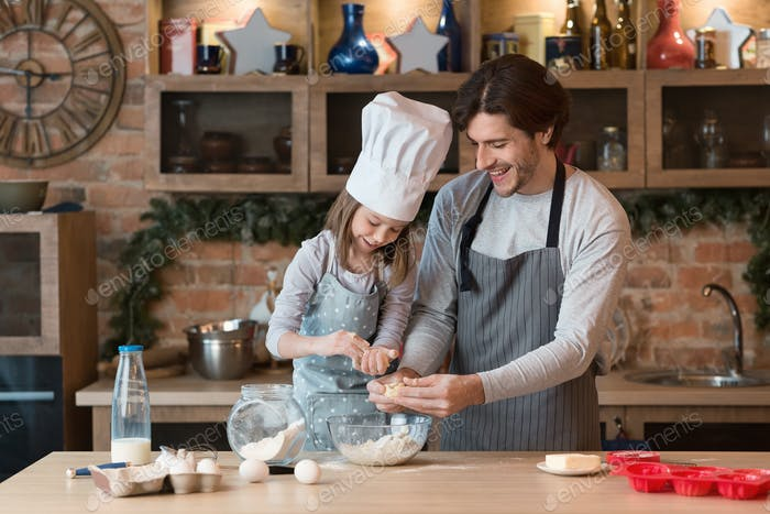 Little Chef. Cute Girl Baking With Father In Kitchen, Preparing Pastry Together