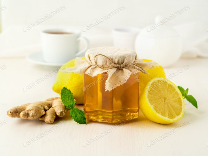 Popular ways to treat a cold - a jar of honey, ginger, mint, lemons on white background, side view