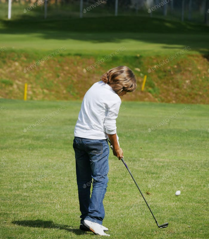 Young golfer performs a golf shot from the fairway.