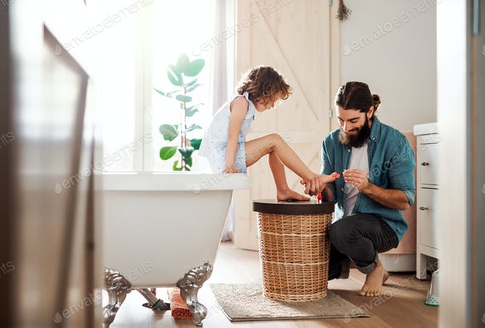 Young father painting small daughter's nails in a bathroom at home.
