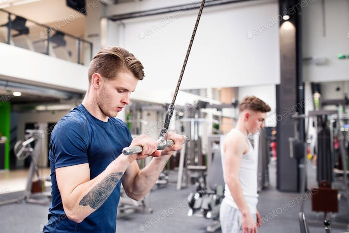 Fit young man in gym working out on pull-down machine.