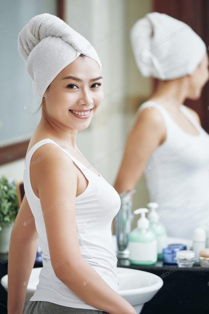 Cheerful ethnic woman in bathroom