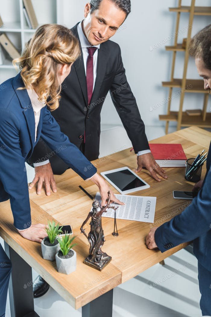 group of lawyers in suits discussing contract together in office
