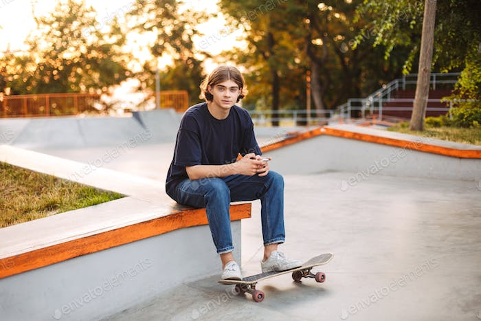 Young skater in black T-shirt and jeans dreamily looking in came