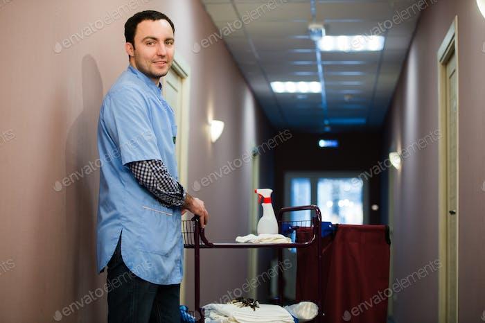 Ein Mann, der auf der Hotelreinigung Crew Personal ist lächelnd mit einem Handtuchvakuum in den Prozess der